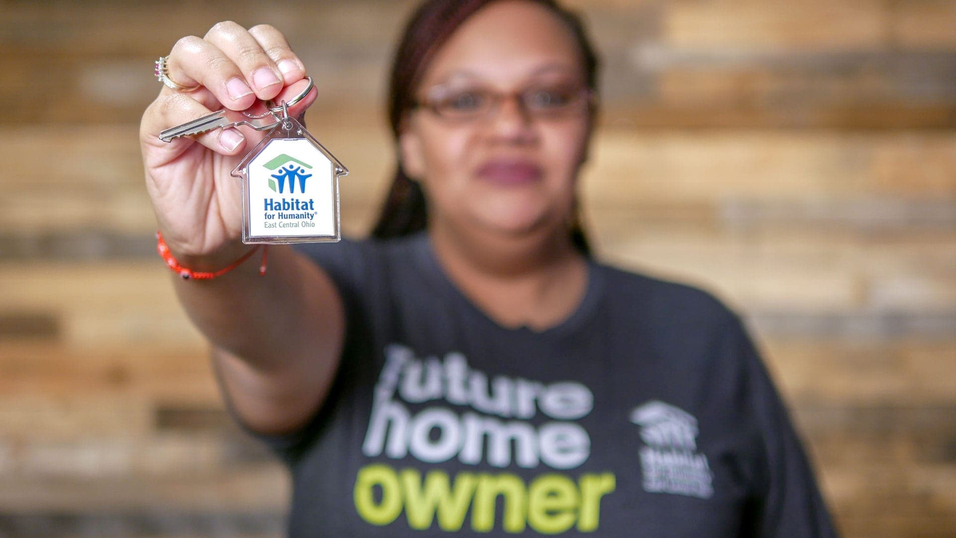 Habitat for Humanity homeowner holding keys to home.